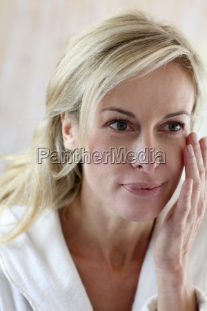 attractive middle aged woman applying comestics