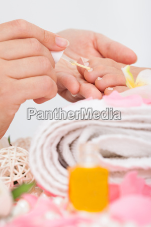 beautician applying nail varnish