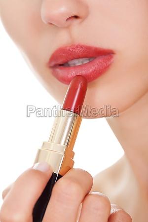 attractive woman applying lipstick