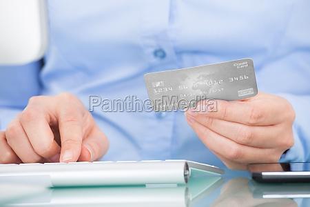 person holding kreditkarte computer benutzen