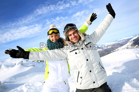 cheerful couple of skiers stretching arms