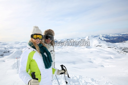 couple of skiers standing on the