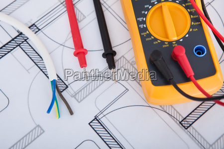 multimeter with wires on blueprint