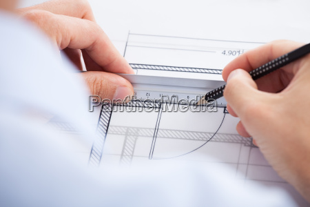 architect using ruler and pencil on