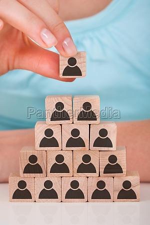 woman stacking wooden team blocks at