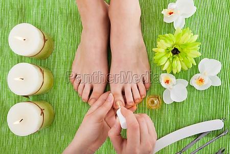 beautician applying nail varnish to woman