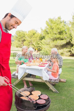 father cooking barbecue for family sitting