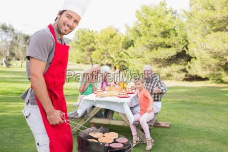 smiling father cooking barbecue for family