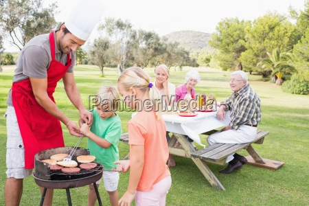 father helping son flip burgers on