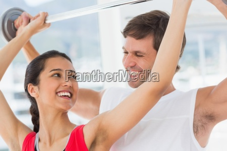 male trainer helping fit woman to