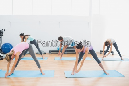 sporty class doing pilate exercises in