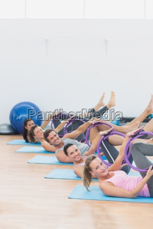 sporty people with exercising rings in