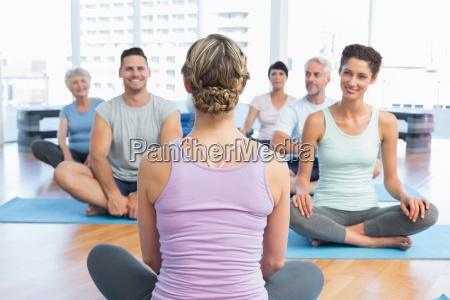 sporty people sitting on exercise mats