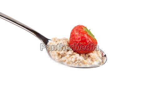 loeffel mit erdbeeren und haferflocken