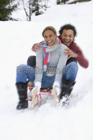 happy mixed race couple sledding down