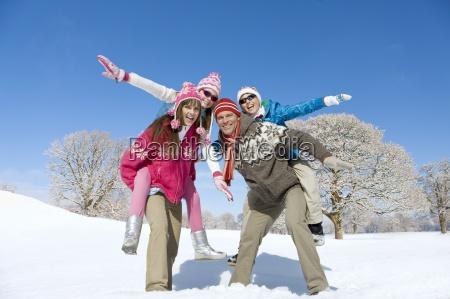 parents carrying exuberant children on back