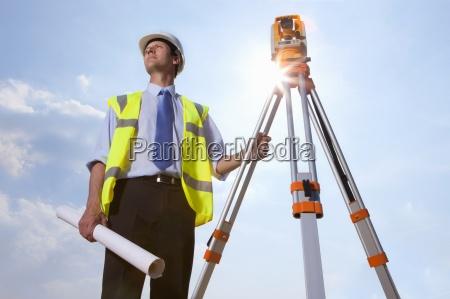 sun shining behind surveyor with blueprint