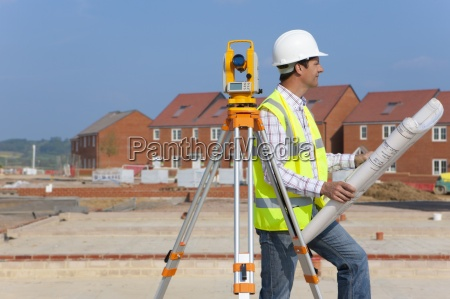 architect with blueprints and theodolite at