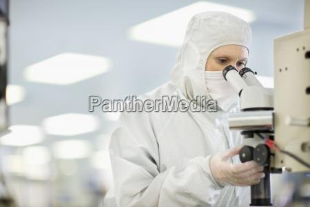 scientist in clean suit using microscope