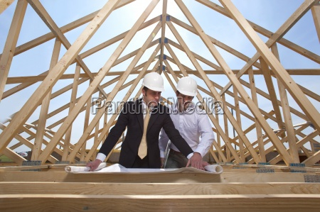 architects reviewing blueprints at construction site