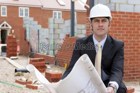 portrait of serious architect holding blueprints