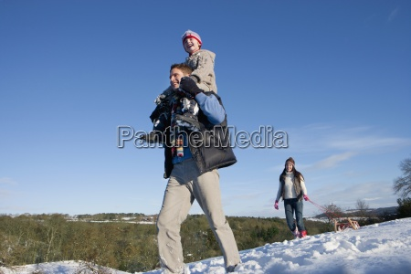 happy family walking with sled in