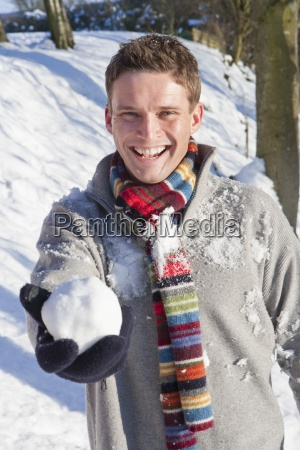 portrait of smiling man holding snowball
