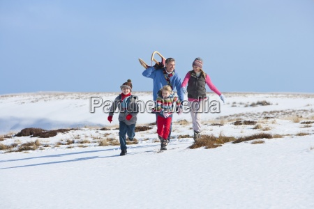 happy family running in snow with