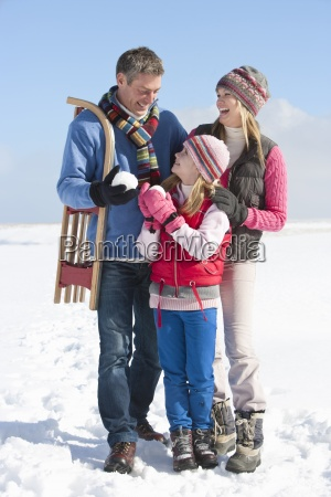smiling parents and daughter with snowball