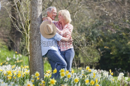 smiling senior couple hugging and leaning