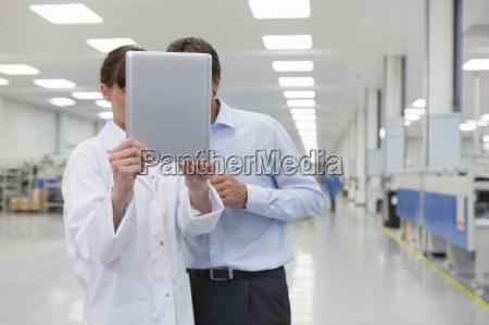 scientist and businessman looking at digital
