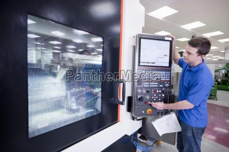 technician operating lathe cutting machine in