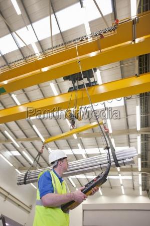 technician operating hoist with raw aluminum