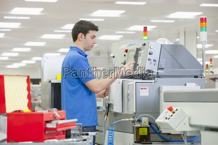 technician using machine in manufacturing plant