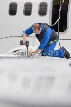 engineer drilling into wing of passenger
