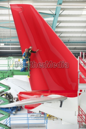engineers on hydraulic lift inspecting tail