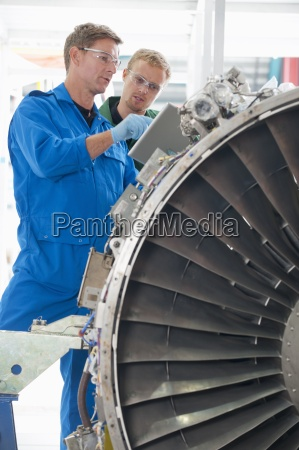 engineers with digital tablet inspecting engine