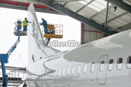engineers on hydraulic lifts inspecting tail