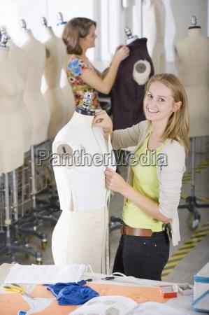mode design student arbeitet an kleidungsstueck