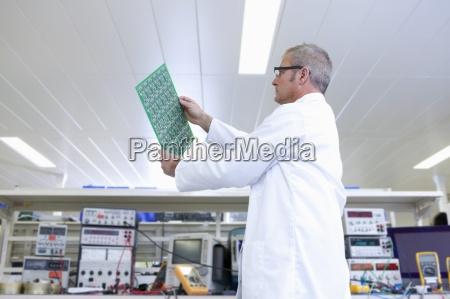 engineer examining printed circuit board at