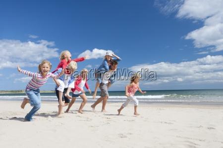 familie auf sonnigen strand laufen