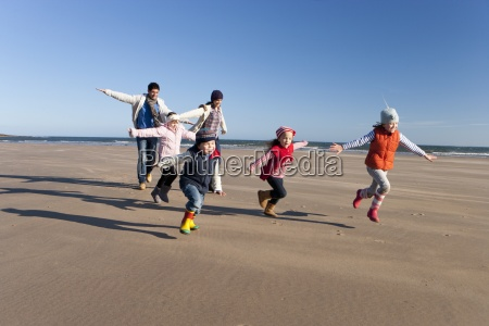 family running with arms outstretched on