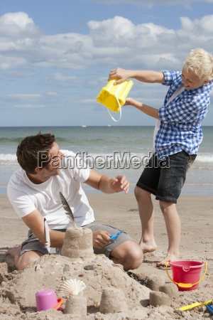 father and son making sandcastle on