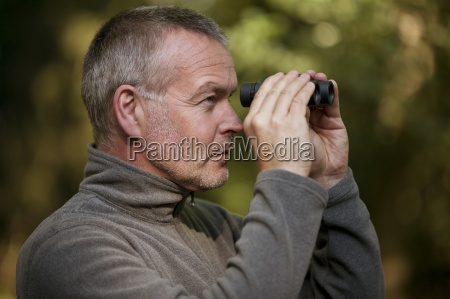 a mature man looking through a