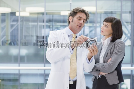 engineer in lab coat and businesswoman