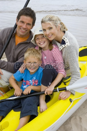 young family sitting in kayak on