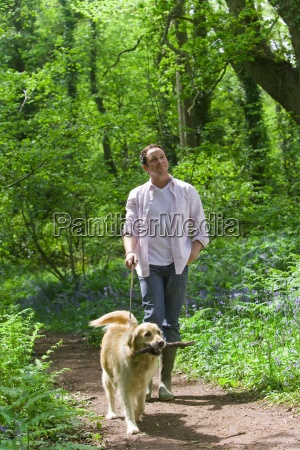 man and dog walking in forest