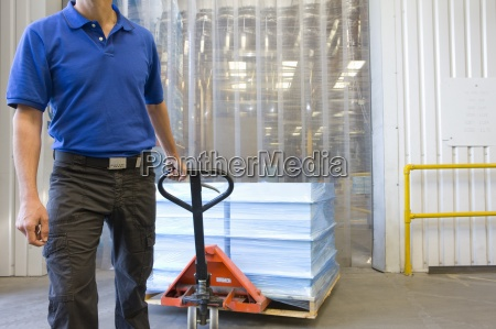 worker pulling inventory on hand truck