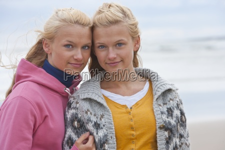 portrait of smiling teenage twin sisters