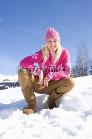 young woman crouching in snow field